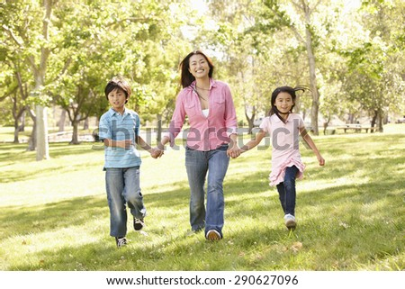 Asian mother and children running hand in hand in park