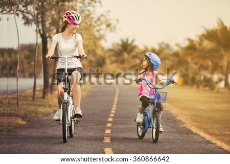 Asian mother and daughter cyclist in the park. - stock photo
