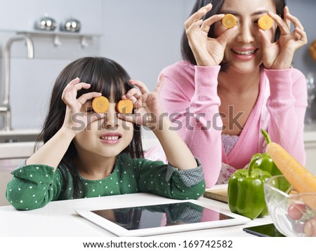 asian mother and daughter having fun in kitchen. - stock photo