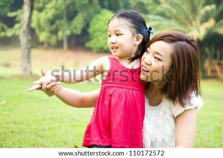 Asian mother and daughter having fun in the garden - stock photo