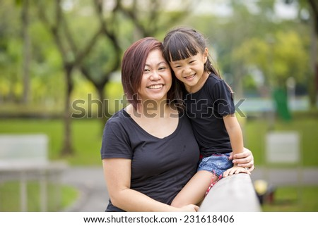Asian mother and daughter having fun in the park - stock photo