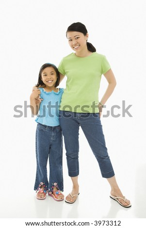 Asian mother and daughter standing with arms around eachother. - stock photo