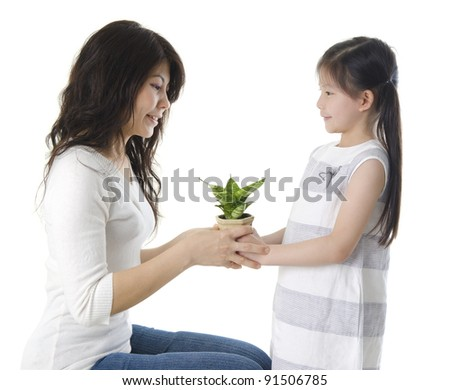 Asian mother and daughter taking care of plant - stock photo