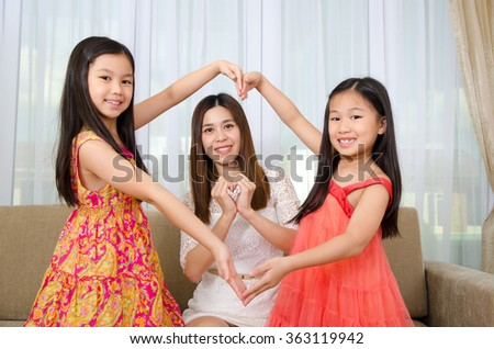 Asian mother and daughters making heart shape with hands - stock photo