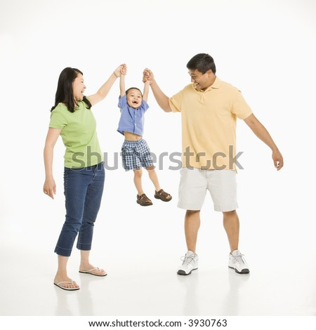 Asian mother and father holding hands with son and lifting him up in front of white background. - stock photo