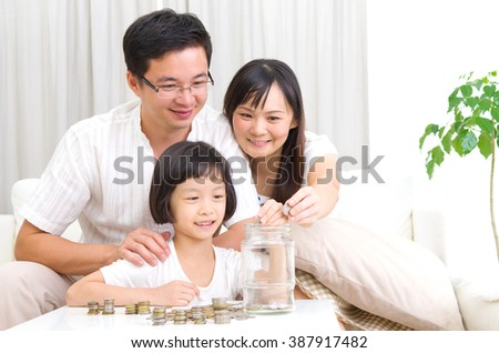 Asian mother and her kid putting coins together into the glass bottle