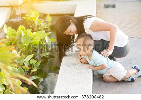 Asian mother and kid having fun time at outdoor in sunset during vacations. - stock photo
