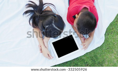Asian mother and son using digital tablet together outdoor. - stock photo