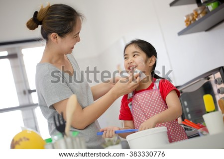 Asian mother cleaning her daughter face in cooking time - stock photo