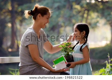 Asian mother cleaning her daughter's face - stock photo