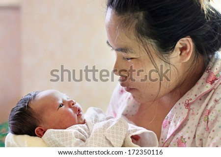Asian Mother holding her Newborn Baby in narrow focus