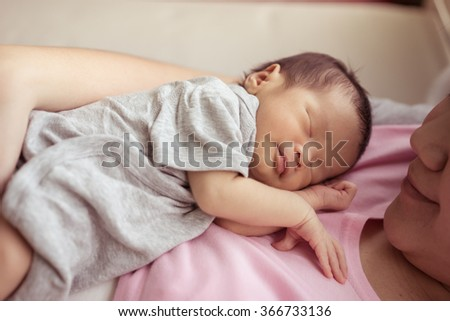 Asian mother holds her  newborn baby - stock photo