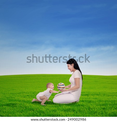 Asian mother playing colorful ball with her baby in spring green field - stock photo
