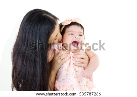 Asian mother playing with baby girl