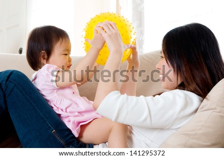 Asian mother playing with her baby girl - stock photo