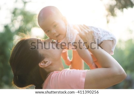 Asian mother playing with her son - stock photo