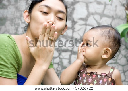 Asian Mother Teach her Baby Girl a Goodbye Kiss - stock photo