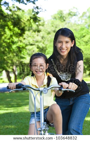 asian mother Teaching daughter To Ride A bicycle - stock photo