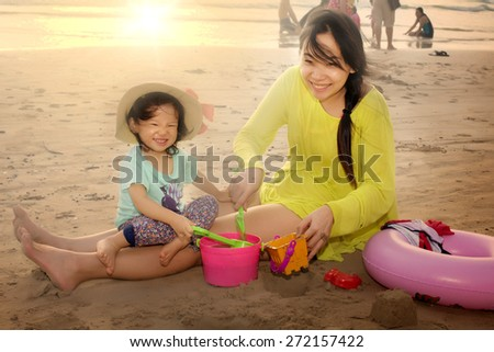 Asian mother with little girl playing on the beach  in the evening. - stock photo
