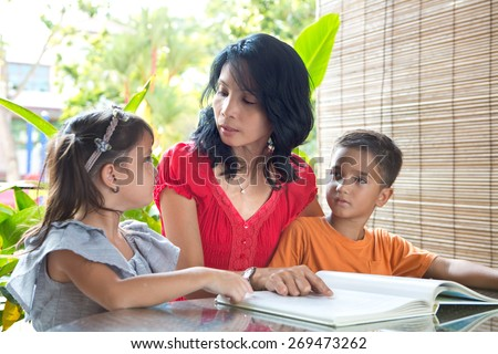 Asian mother with young daughter and son reading a story book together in a home environment - stock photo