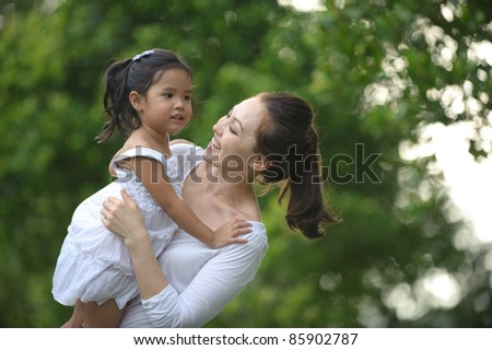 Asian mum and daughter enjoying each others company in the park