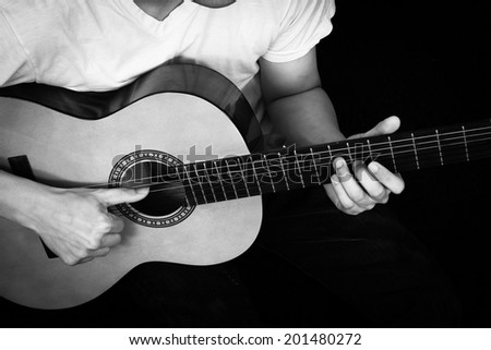 Asian Musician plays Acoustic Guitar, B&W film processed - stock photo