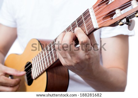 Asian musician plays acoustic guitar, isolated - stock photo
