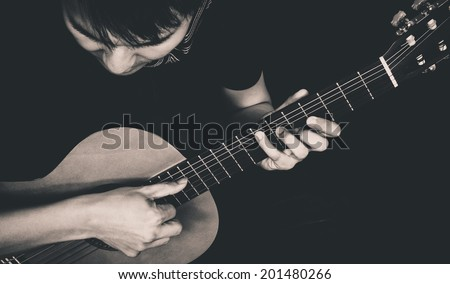 Asian Musician plays Acoustic Guitar, old B&W film processed - stock photo