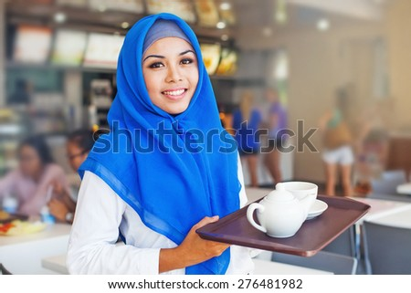 asian muslim girl wearing hijab working as a waitress in cafe - stock photo