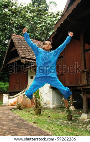Asian muslim male in traditional Baju Melayu jumping excitedly in front of a village house