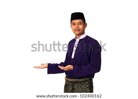 Asian muslim male with traditional Malay costume in present text space action, Baju Melayu - stock photo