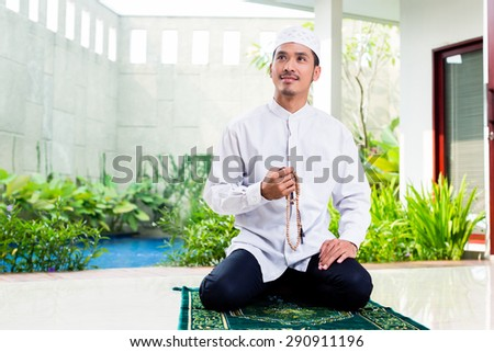 Asian Muslim man praying at home sitting on prayer carpet in his house in front of the tropical garden