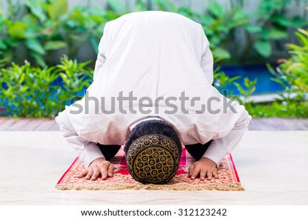 Asian Muslim man praying on carpet wearing traditional dress - stock photo