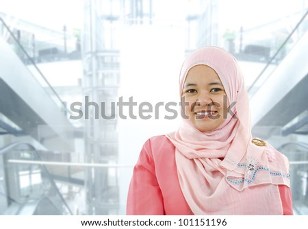Asian Muslim woman standing on modern office background - stock photo