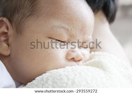 Asian Newborn Baby Girl Sleeping on Her Mother Shoulder. - stock photo