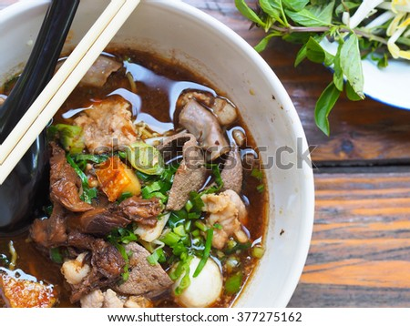 asian noodle soup with pork meatball with fresh vegetable on wood table vintage style, simply food, street food, hot and spicy noodle soup, asian food - stock photo