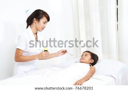 asian nurse giving medication to a child patient