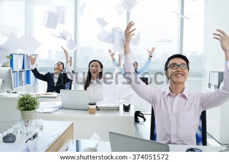 Asian office workers throwing documents in the air