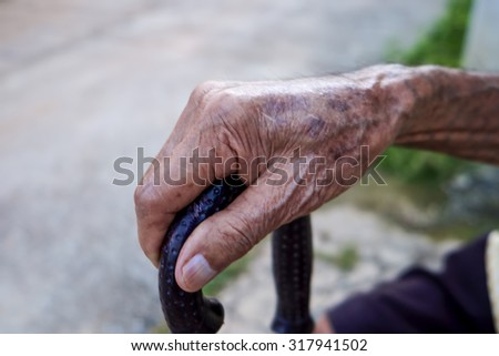 Asian old man sitting with his hands on a  walking stick. - stock photo