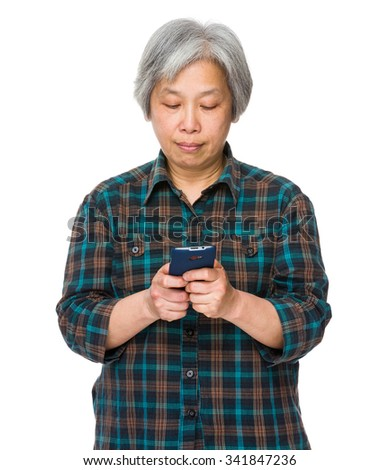 Asian Old woman play the game on mobile phone - stock photo
