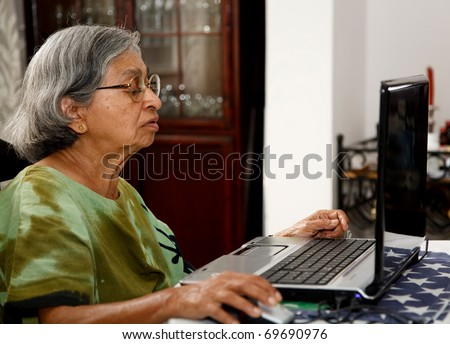 Asian old woman using computer - stock photo