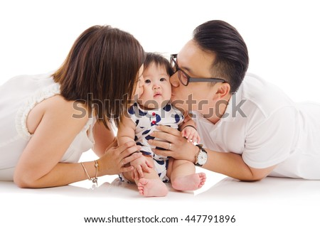 Asian parent kiss their baby girl - stock photo