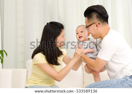 Asian parent playing with their baby boy