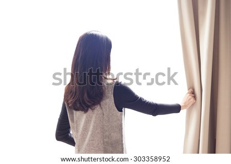 Asian portrait beautiful woman opening curtains on white background - stock photo