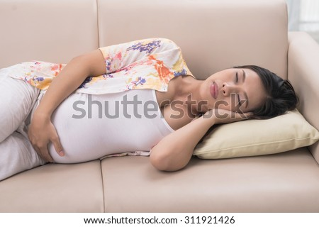 Asian pregnant woman sleeping on the sofa at home - stock photo