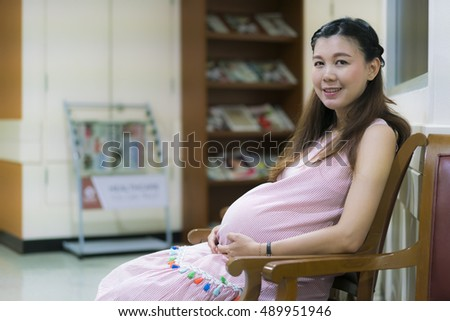 Asian pregnant woman waiting for doctor