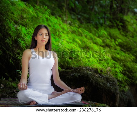 Asian pretty woman doing yoga exercises in the green nature park - stock photo
