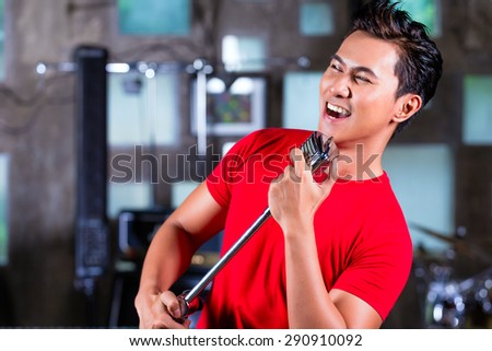 Asian professional musician recording new song or album CD in studio - stock photo