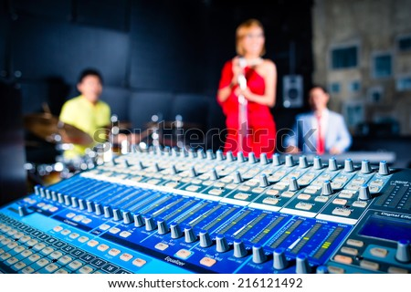 Asian professional recording studio mixing new song of band - stock photo