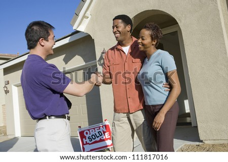 Asian real estate agent with couple buying new house - stock photo